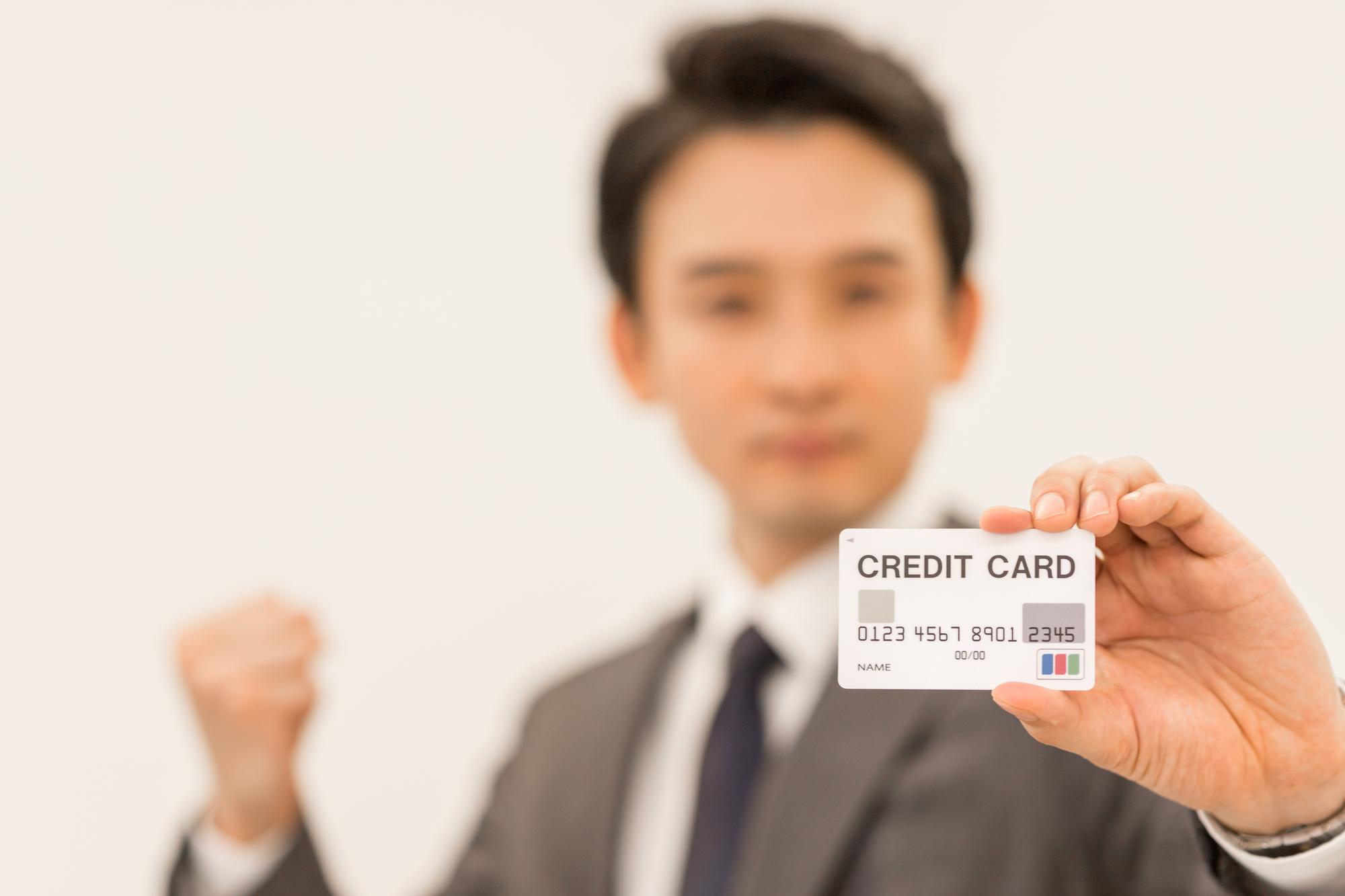 クレジットカードを持ってガッツポーズする人